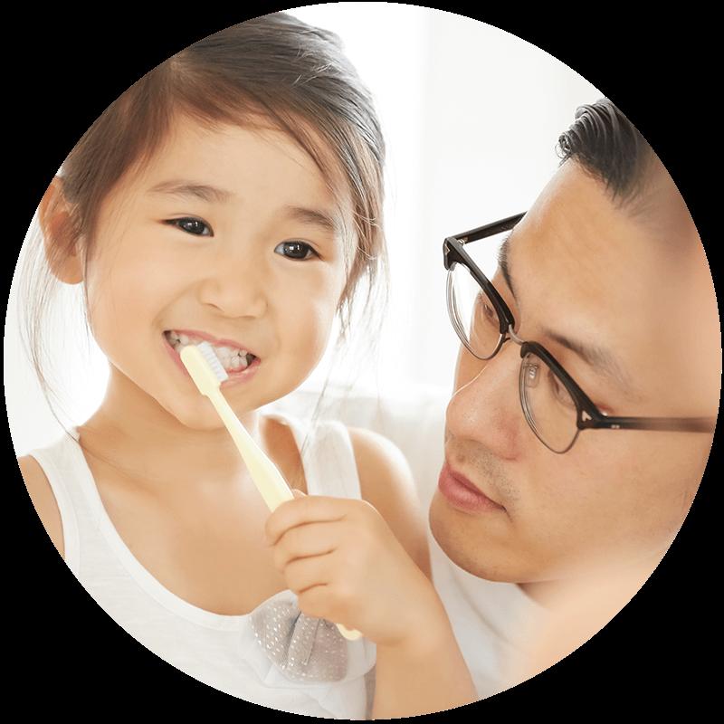 歯磨きしている子供と見守る父親